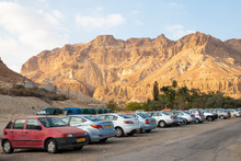 Car Park At Ein Gedi - National Park And Resort View Of  Negev Desert Mountain Landscape In Israel. A Small Group Of Hikers Walking On The Path.
