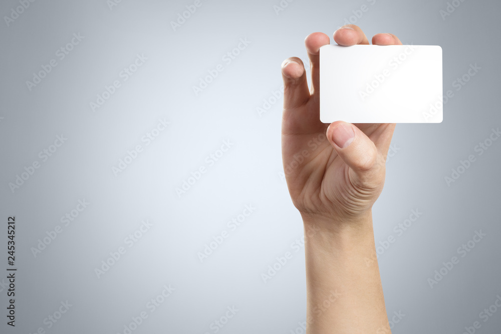 Fototapeta Hand holding a blank card or a ticket/flyer on gray background