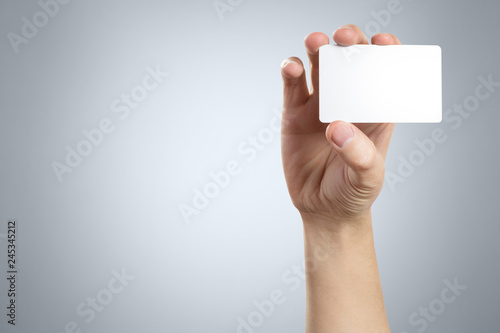 Obraz Hand holding a blank card or a ticket/flyer on gray background - fototapety do salonu
