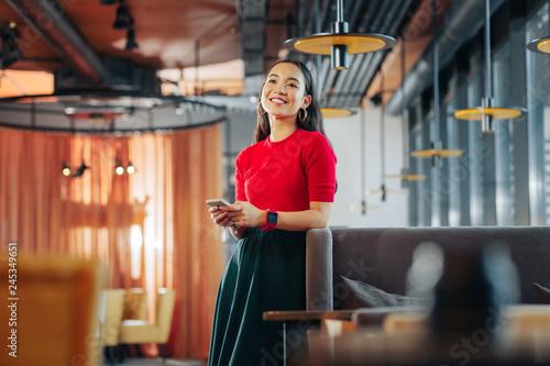 Obraz na płótnie Cheerful dark-haired woman waiting for boyfriend in restaurant