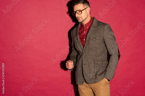 confident stylish man in formal wear and glasses on red background with copy space