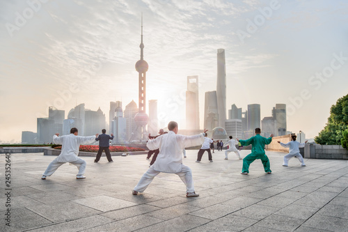 Photo Stands Shanghai Group of people practicing Tai Chi Chuan am Bund, Shanghai, China