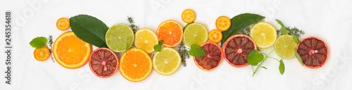 Fototapeta  many different fresh citrus fruits on white crumpled paper background