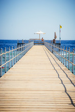 A Wooden Pier With Sun Lounger...