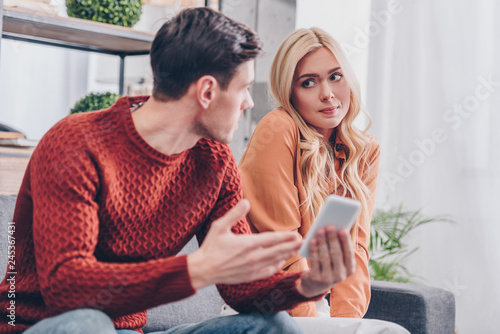 emotional young man holding smartphone and looking at confused girlfriend sittin Wallpaper Mural