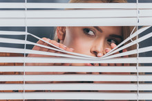 Young Woman Looking Away And Peeking Through Blinds, Mistrust Concept
