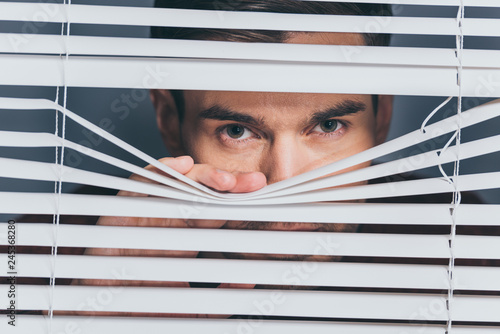 Photo suspicious young man looking at camera through blinds, mistrust concept
