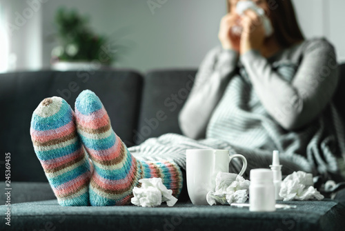 Obraz Sick woman with flu, cold, fever and cough sitting on couch at home. Ill person blowing nose and sneezing with tissue and handkerchief. Woolen socks and medicine. Infection in winter. Resting on sofa. - fototapety do salonu