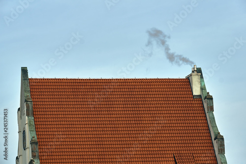 Foto  A historic building with a roof made of red tiles and a smoking chimney in Poznan
