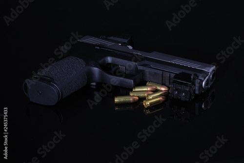 Photo gun and bullets on black background