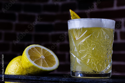 Carta da parati A classic recipe for whiskey sour - with bourbon, cane syrup and lemon juice, garnished with orange