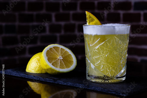 Fototapeta A classic recipe for whiskey sour - with bourbon, cane syrup and lemon juice, garnished with orange