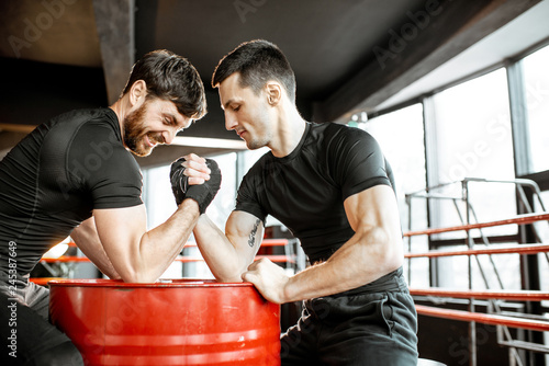 Two young athletes in black sportswear having a hard arm wrestling competition o Canvas Print