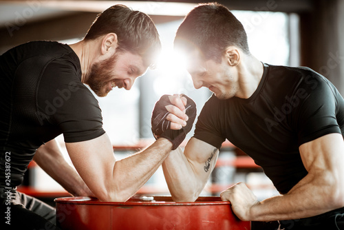 Photo  Two young athletes in black sportswear having a hard arm wrestling competition o