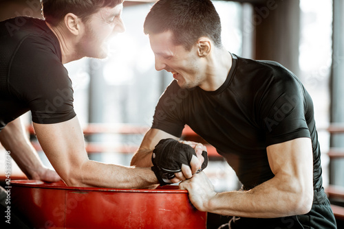 Fotografía  Two young athletes in black sportswear having a hard arm wrestling competition o