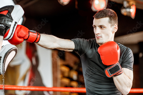 Athletic man fighting during the training with boxing trainer on the boxing ring Fototapeta