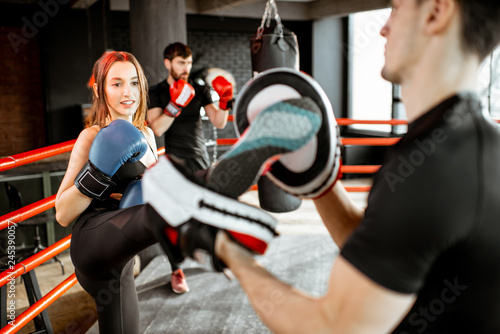 фотография Young woman training to box with personal coach on the boxing ring at the gym