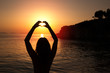 Silhouette of a woman making a heart with her hands and the sunset inside