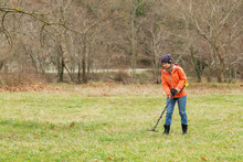 A Girl In An Orange Jacket With A Metal Detector In His Hands, Is On The Field In Search Of Antiquity