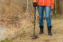 Close-up Of The Girl's Legs And A Metal Detector, On The River Coast