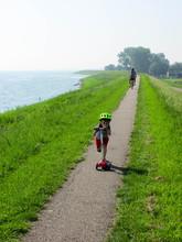 Little Boy On A Scooter In A Helmet Rolls Along A Canal, Hoorn, Netherlands