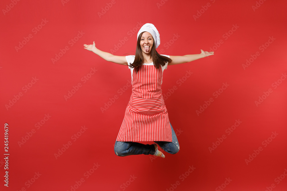 Fototapeta Housewife female chef cook or baker in striped apron white t-shirt, toque chefs hat isolated on red wall background. Full length portrait housekeeper woman jumping high up. Mock up copy space concept.