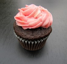 Chocolate Cupcake With Pink Frosting Over Black Background