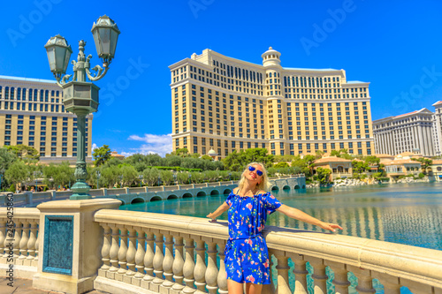 Photo Stands Las Vegas Caucasian lifestyle woman enjoying in Las Vegas Strip. Happy blonde tourist in Nevada, USA. Pool with fountains at popular Hotel Casino. Las Vegas cityscape with blue sky. Architecture background.