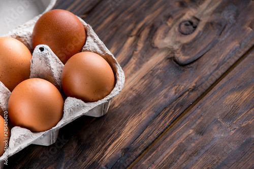 chicken eggs on old wooden board with blank space for text
