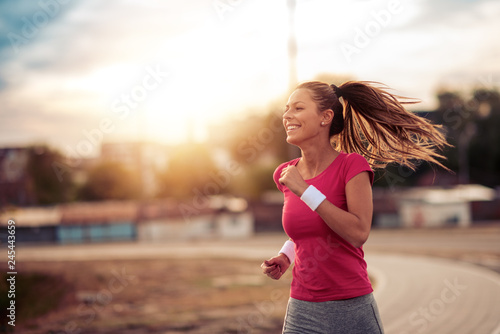 Foto  Young woman running in the city street