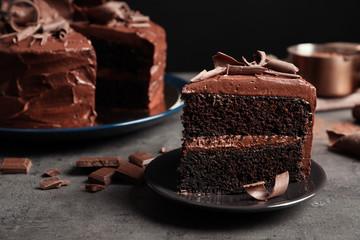 Ploča s kriškom ukusne domaće čokoladne torte na stolu