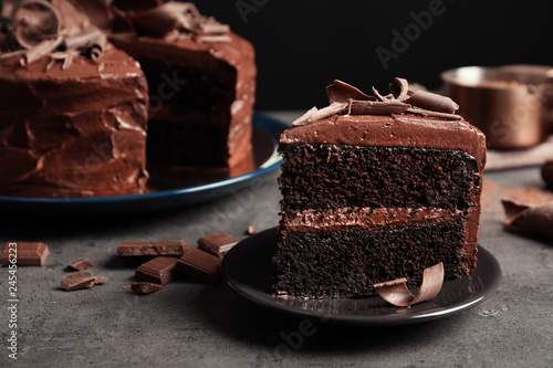 obraz lub plakat Plate with slice of tasty homemade chocolate cake on table