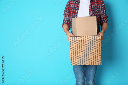 Man with moving boxes on color background. Space for text