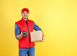 canvas print picture - Male courier with parcel and payment terminal on color background. Space for text