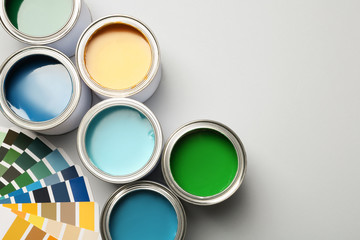 Paint cans and color palette on white background, top view. Space for text