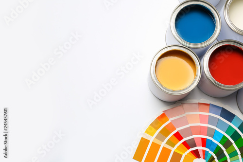 Different paint cans and color palette on white background, top view. Space for text