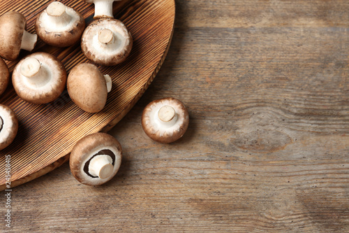 Fresh champignon mushrooms and cutting board on wooden table, top view with space for text