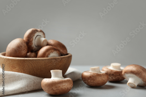 Fresh champignon mushrooms and wooden bowl on table, space for text