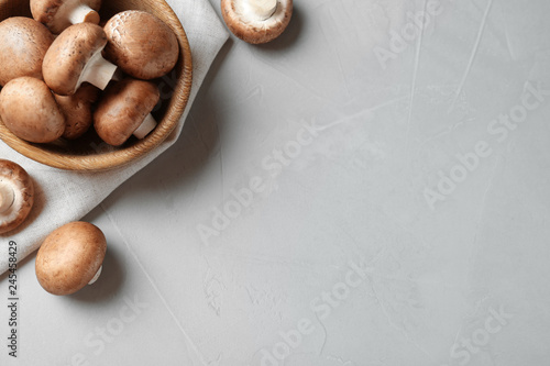 Fresh champignon mushrooms and wooden bowl on table, top view. Space for text