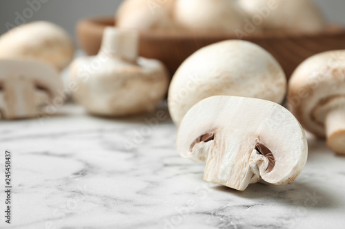Fresh champignon mushrooms on marble table, closeup. Space for text