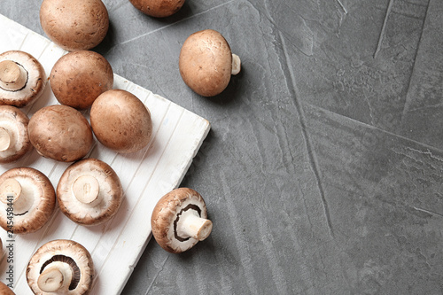 Flat lay composition with fresh champignon mushrooms on grey background, space for text