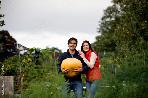 Photo Young smiling couple standing on allotment holding large pumpkin smiling at came
