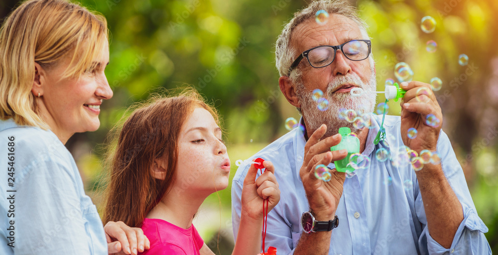 Fototapety, obrazy: Happy family blows soap bubbles together while going vacation on weekend in the garden park in summer. Kid education and family activities concept.
