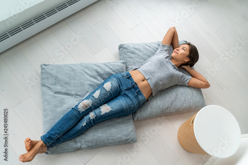 Deurstickers Ontspanning Home lifestyle happy Asian woman relax lying down on living room floor pillows relaxing contemplative looking at windows. New condo apartment satisfaction homeowner young girl enjoying house.