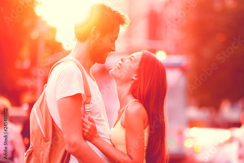 Couple in love laughing hugging looking at each other in sunset. People falling in love, happiness fun. Interracial young couple embrace on date. Caucasian man Asian woman on city street lifestyle.