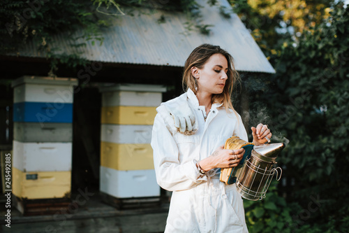 Beekeeper with the smoker and her bee hives Canvas Print