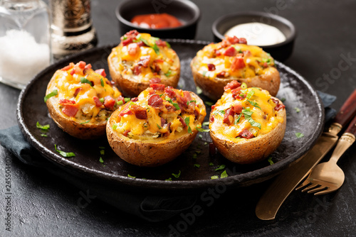 Fototapeta Hot baked potato topped with bacon, green onions and cheddar cheese. obraz
