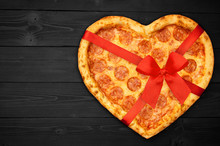 Pizza Pepperoni Shaped Heart With Red Ribbon Bow For Valentine's Day On Rustic Dark Black Background. Top View. Flat Lay