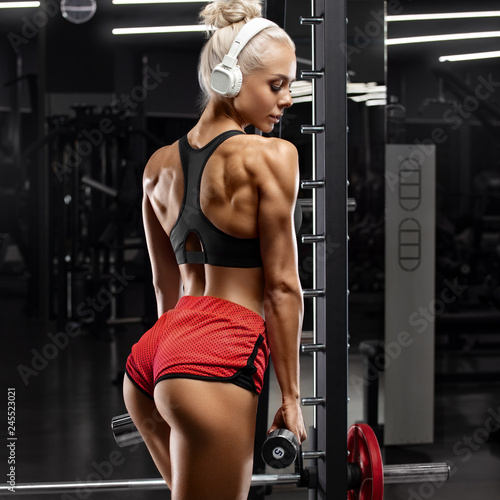 Fitness sexy woman working out in gym. Girl with muscular back. Sexy beautiful butt in thong