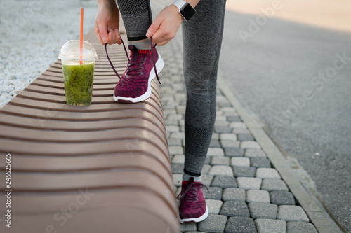 Valokuva  Green detox smoothie cup and woman lacing shoes before workout.